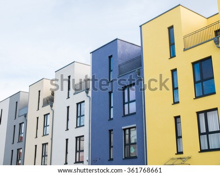 Low Angle Architectural Exterior Detail of Colorful Modern Row Townhouses with Rooftop Patios, Angled in front of Cloudy Blue Sky