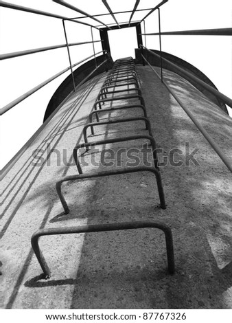 low angle black and white shot of a old tower with metallic stairway