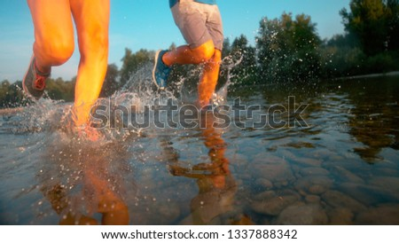 LOW ANGLE: Carefree active tourists jogging in the refreshing river on a beautiful spring morning. Unrecognizable athletic couple unwind by going for a evening jog along the sunlit forest stream. #1337888342