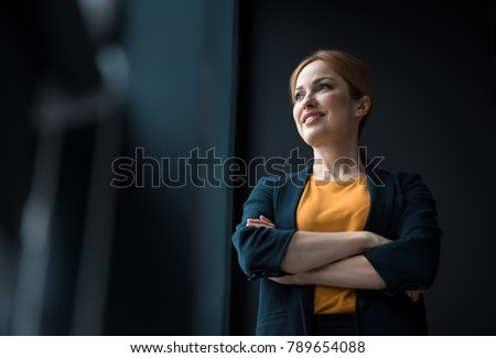 Low angle cheerful girl with crossing arms situating in apartment. Job concept
