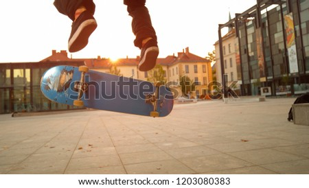 LOW ANGLE, CLOSE UP: Blue skateboard flipping underneath the young and athletic skateboarder's feet. Unrecognizable male skateboarding and doing tricks in the urban streets on idyllic autumn evening.