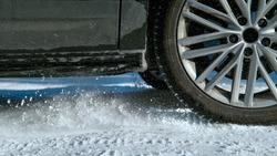LOW ANGLE, CLOSE UP, DOF: Detailed shot of car's spinning wheels as it slides along snowy road. Powerful vehicle's wheels spin in place and throw up pieces of snow while gaining traction on a trail.