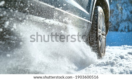 LOW ANGLE, CLOSE UP, DOF: Fresh snow flies up from a large vehicle's spinning wheel. Car's wheels spin and spew up pieces of snow and snowflakes as it attempts to gain traction on the slippery road. Stockfoto ©