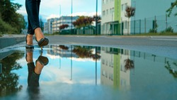 LOW ANGLE, CLOSE UP, DOF: Unknown businesswoman in heels steps into small puddle on the side of the empty asphalt road. Unrecognizable young woman wearing heels walks into a glassy pool of water.