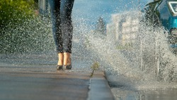 LOW ANGLE, CLOSE UP, DOF: Unrecognizable young woman wearing high heels gets splashed with water as inconsiderate driver drives their car into a deep puddle at the side of the empty asphalt road.