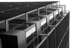Low angle close-up fragment of industrial building with lift shaft and perforated panels. Modern industry and minimal architecture background with modular structure of glass and metal framework.