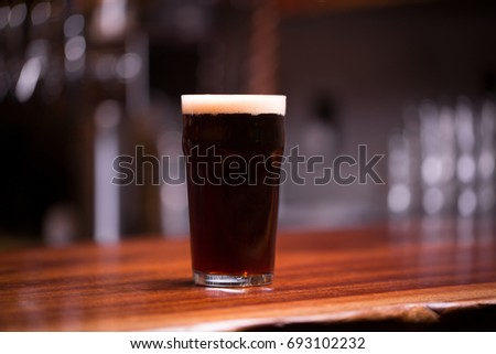 Low angle close up perspective of traditional tumbler nonic pint shape beer glass filled with dark malt stout with foam head on wood grain counter top bar with blurry restaurant background Stock photo ©