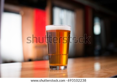 Low angle close up perspective of traditional tumbler pint shape beer glass filled with golden malt and hoppy India pale ale with foam head on wood counter top bar with blurry restaurant background Stock photo ©