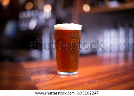 Low angle close up perspective of traditional tumbler pint shape beer glass filled with golden malt and hoppy India pale ale with foam head on wood counter top bar with blurry restaurant background