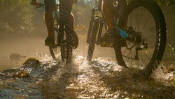 LOW ANGLE CLOSE UP: Two unrecognizable persons riding new mountain bikes across the sunlit stream and splashing water. Bright sun rays illuminate the river as men ride bikes through the dark forest.