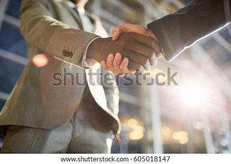 Low angle closeup shot of two business partners in handshake: unrecognizable African -American businessman shaking hands with Caucasian colleague in hall of modern glass office building at night time #605018147