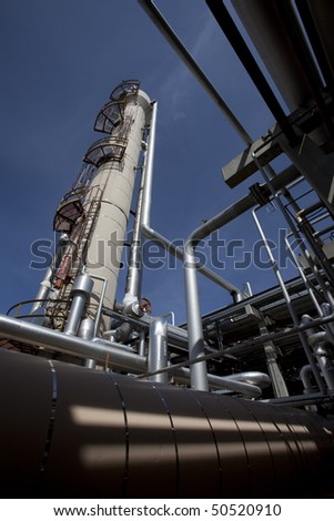Low angle, exterior view of a tower at a gas compressor plant with large pipes in the foreground. Vertical shot.