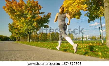 LOW ANGLE: Fit woman goes for a jog around the scenic park full of trees changing their leaves on a sunny autumn day. Unrecognizable energetic girl in grey jogs along the beautiful fall colored avenue