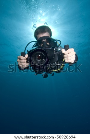 Low angle Front view of an Underwater camerman filming in crystal clear water. MORE INFO: Model released