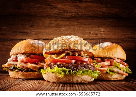 Low angle front view on three large chicken, beef and shrimp burgers stuffed with delicious toppings over wooden table