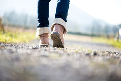 Low angle ground level view with shallow dof of the feet of a woman in jeans and ankle high leather boots walking along a rural path away from the camera.