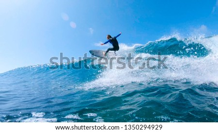 LOW ANGLE, LENS FLARE: Cheerful surfer riding big foaming ocean wave in sunny nature. Stoked man having fun surfing a large wave on his cool surfboard in the summer sun near the idyllic Canary Islands #1350294929