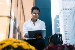 Low angle of African American woman smirking and using tablet while sitting near bag and working on business project on street