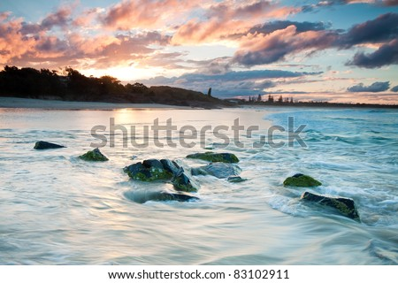 low angle of australian seascape at sunset with rocks in foreground (cabarita,nsw,australia)