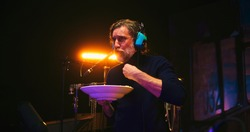 Low angle of bearded mature male sound designer chewing food and speaking in microphone while creating soundtrack for film in studio