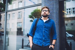 Low angle of bearded young man in eyeglasses and casual clothes with backpack over shoulder observing activity on street in summer day