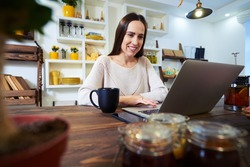 Low angle of Caucasian woman working at home in front of a laptop. Using touchpad. Young businesswoman working at home in the morning