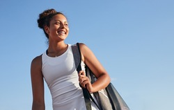 Low angle of cheerful young African American sportswoman with tennis racket bag over shoulder smiling and looking away against blue sky