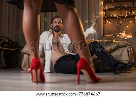 Low angle of confident man inviting his lover to bed. He is sitting on floor with bare torso and stretching hand up by gesture. Gracious female feet standing on red high feel shoes in front of him