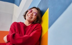 Low angle of delighted young woman in trendy sweatshirt and sunglasses smiling for camera and leaning on multicolored wall