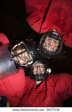 Low angle of female hockey players in huddle smiling.