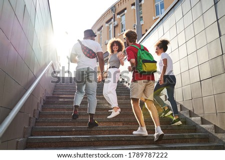 Low angle of four merry people chatting while going upstairs out of pedestrian subway in city centre Foto stock ©