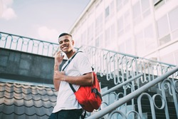 Low angle of happy African American male in casual clothes with toothy smile looking at camera while going downstairs and speaking on smartphone