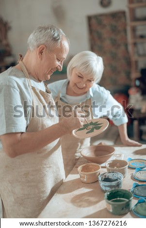 Low angle of happy male artist in apron painting decorative plate with paintbrush while making ornament on earthenware in potter's studio. Gray-haired wife is looking at his work indoors. Ceramic art
