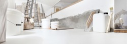 Low angle of indoor shot of construction or building site of home renovation with tools on white floor with paint buckets and primer jerry can