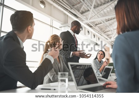 Low angle of managers sitting in the office and listening to speech of their partner