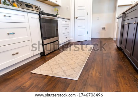 Low angle of new construction modern kitchen with white cabinets and hardwood floors