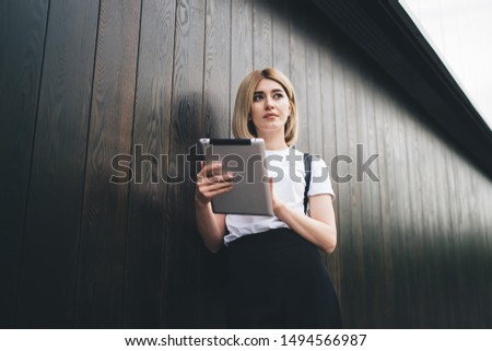 Low angle of pensive charming female student looking away pensively while standing and leaning on wooden wall and using tablet
