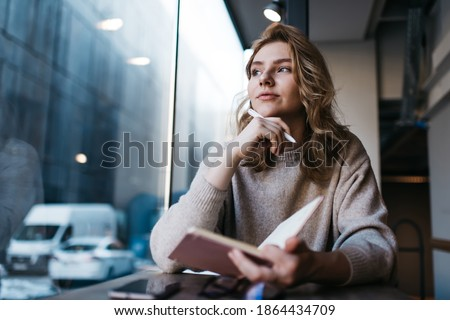 Low angle of pensive young female writer looking away and thinking while working on new article sitting in modern cafe with notebook and smartphone Photo stock ©