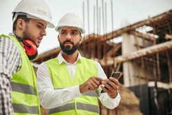 Low angle of professional male technicians in workwear and hardhats using smartphone while discussing engineering plan on construction site of contemporary building