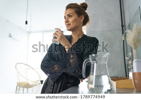 Low angle of smiling female in black dressing gown standing in kitchen with glass of water ストックフォト ©