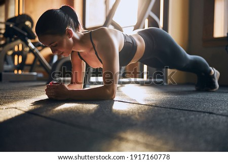 Low angle of smiling pretty female standing in plenk position on elbows while training in studio Stock photo ©