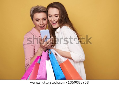 Low angle of stylish surprised ladies wearing fashionable blouses. They are looking at cellphone while holding colorful paper bags in arms against yellow background . Black friday sale concept