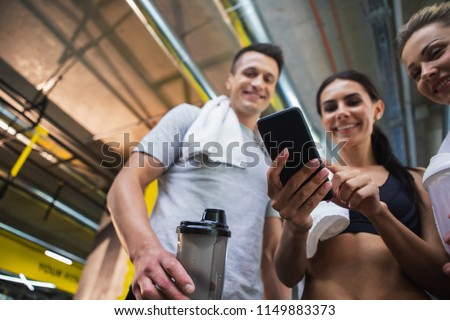 Low angle of three sporty people using mobile phone in gym with focus on gadget. Two girls and guy are standing and looking at device. They are holding water flasks and towel