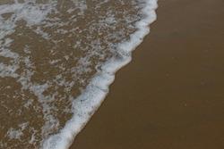 Low angle panoramic view of foamy sea waves of Arabian Sea swashing on sandy Gokarna Main Beach situated on the West Coast of Karnataka in India.