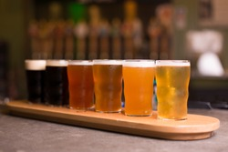 Low angle perspective close up of craft beer tasting flight at local brewery of small pint glasses in row on wooden tray with rainbow variety of golden yellow hoppy ales to dark malt stouts on bar