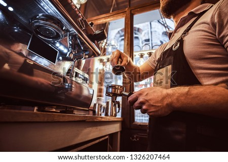 Low angle photo of a barista holding a portafilter, working in the coffee shop or restaurant