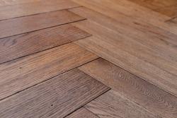 Low angle photo of orange brown aged old hundred year old hardwood oak parquet tile floor of herringbone (fish tale) flooring