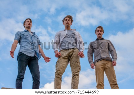 Low angle photo of three guys standing high above, looking down, dramatic vantage point, cinematic look