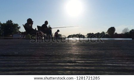 Low angle photo of three young men silhouette recreational fishing angling for pleasure done with  rod reel line hooks and any one of a wide range of baits to catch fish