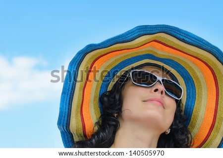 Low angle portrait of a beautiful woman in a wide brimmed colourful striped straw sunhat against a blue sky